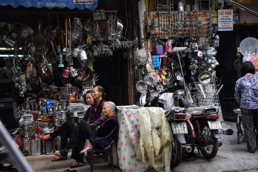 Three women sitting outside a store on an street where only metal fabrication takes place