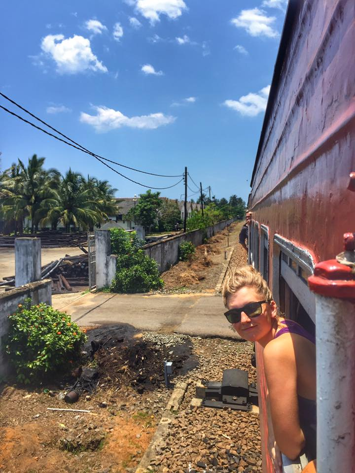 Blond haired woman with her head out the window of a train on a sunny day in Sri Lanka