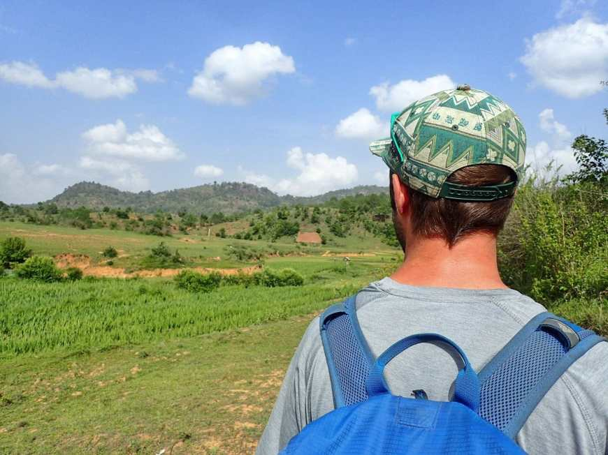 Travel blogger Tj looking out over green fields and hills under a blue sky on our first day of trekking