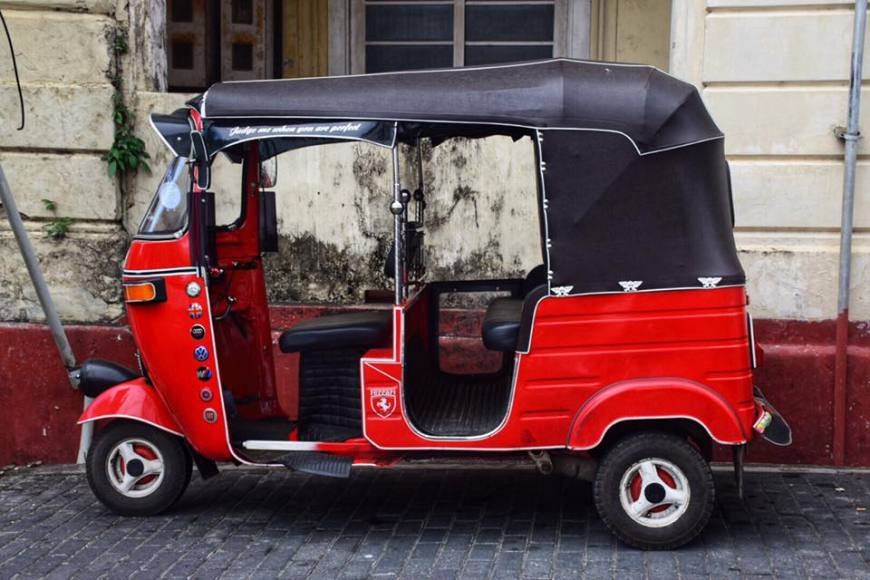 Bright red tuk tuk with a black top on a street in the old fort town of Galle, Sri Lanka