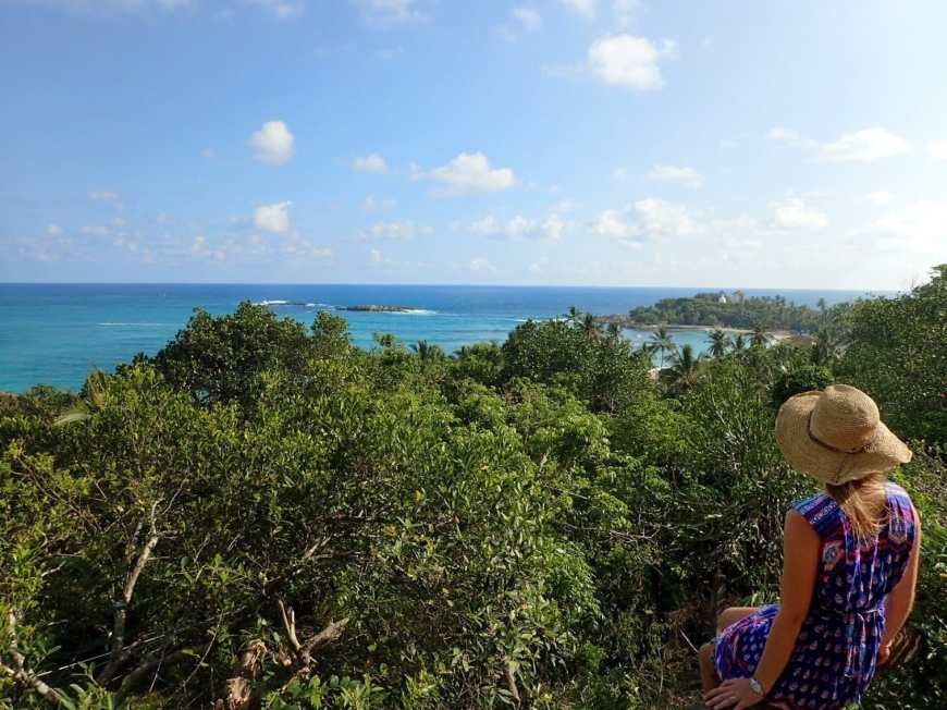 Viewpoint with a beautiful view of unawatuna beach over a tropical green forest with a woman in a sun