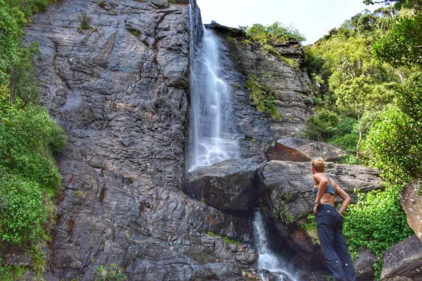Woman standing below a waterfall in hiking clothes as she marvels up at the cascade of water 20 meters high in Nuwara Eliya