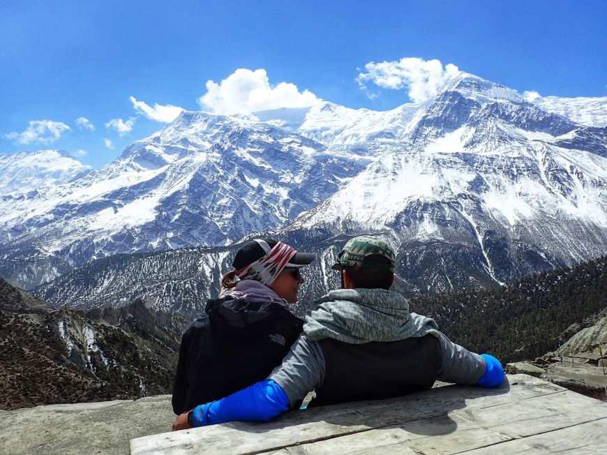 Travel bloggers, Alli & TJ Enjoying a trekking break to take in the vista of the Himalayan mountains