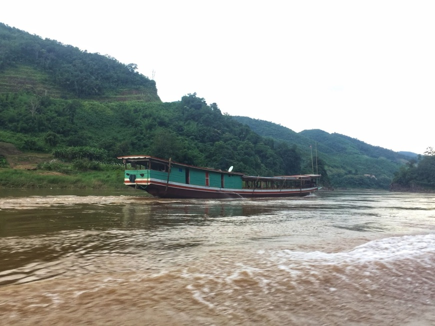 Traditional, long river boat traveling down the river in Laos