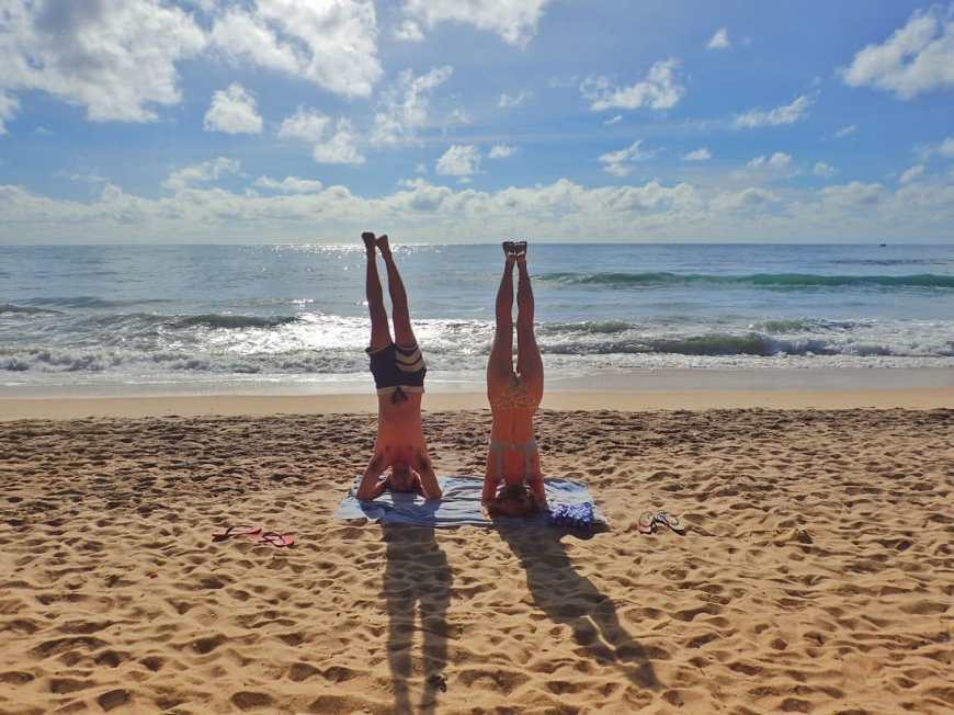 Travel and adventure blogging couple doing headstands together on the sandy beach in the early morning