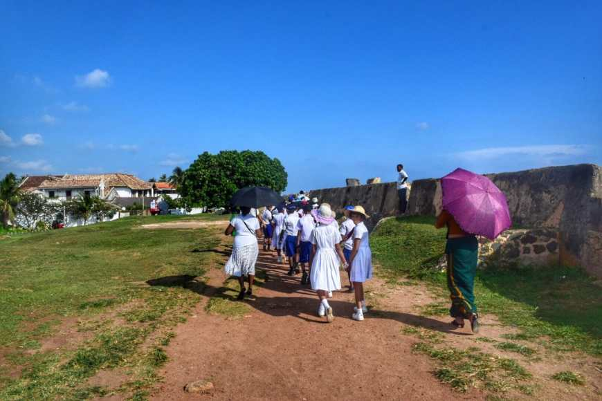 Group of Sri Lankan students in white dresses walking along the fort wall in Galle, Sri Lanka at the end of the school day