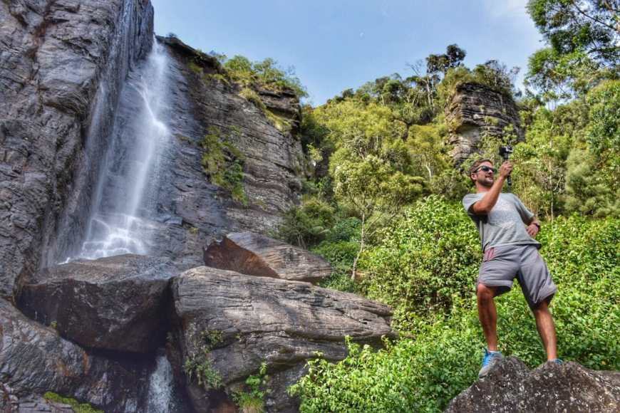 Travel Blogger standing on a rock filming with his go pro in front of a large waterfall in Nuwara Eliya, Sri Lanka