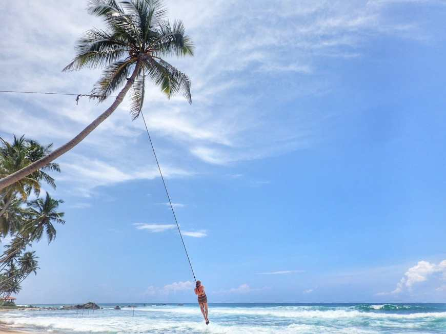 Woman swinging away above the ocean on a palm tree rope swing