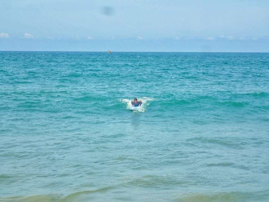 Travel and adventure blogger learning to surf and catching and small wave in Arugam Bay