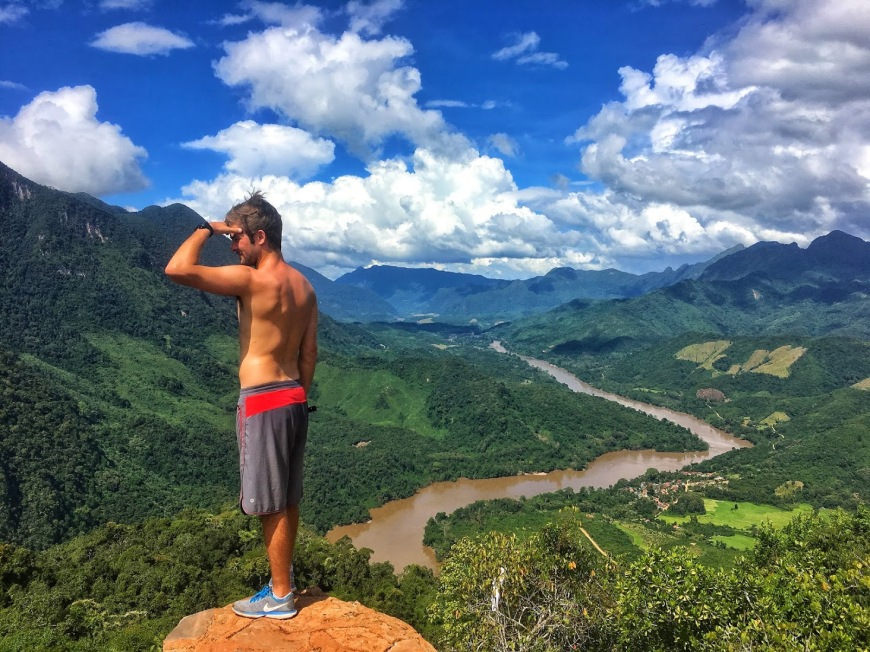 Man standing at the top of the Viempoint in Nong Khiaw, Laos looking out over the valley and Nam Ou River
