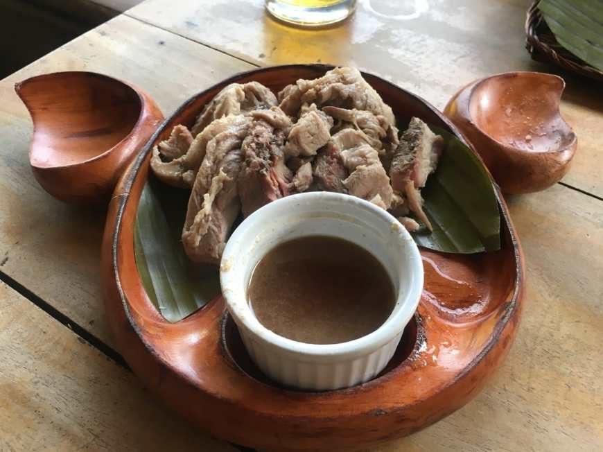 A plate of The Philippine's famous Lechon dish served in a wooden plate shaped like a pigs head