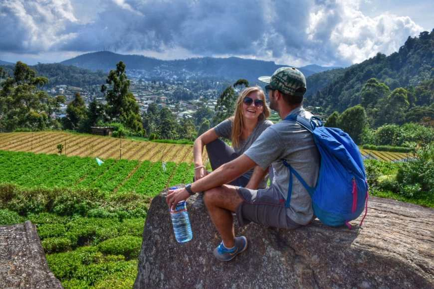 Travel and adventure couple laughing as they sit on an enormous boulder overlooking tea fields and the town of Nuwara Eliya in Sri Lanka