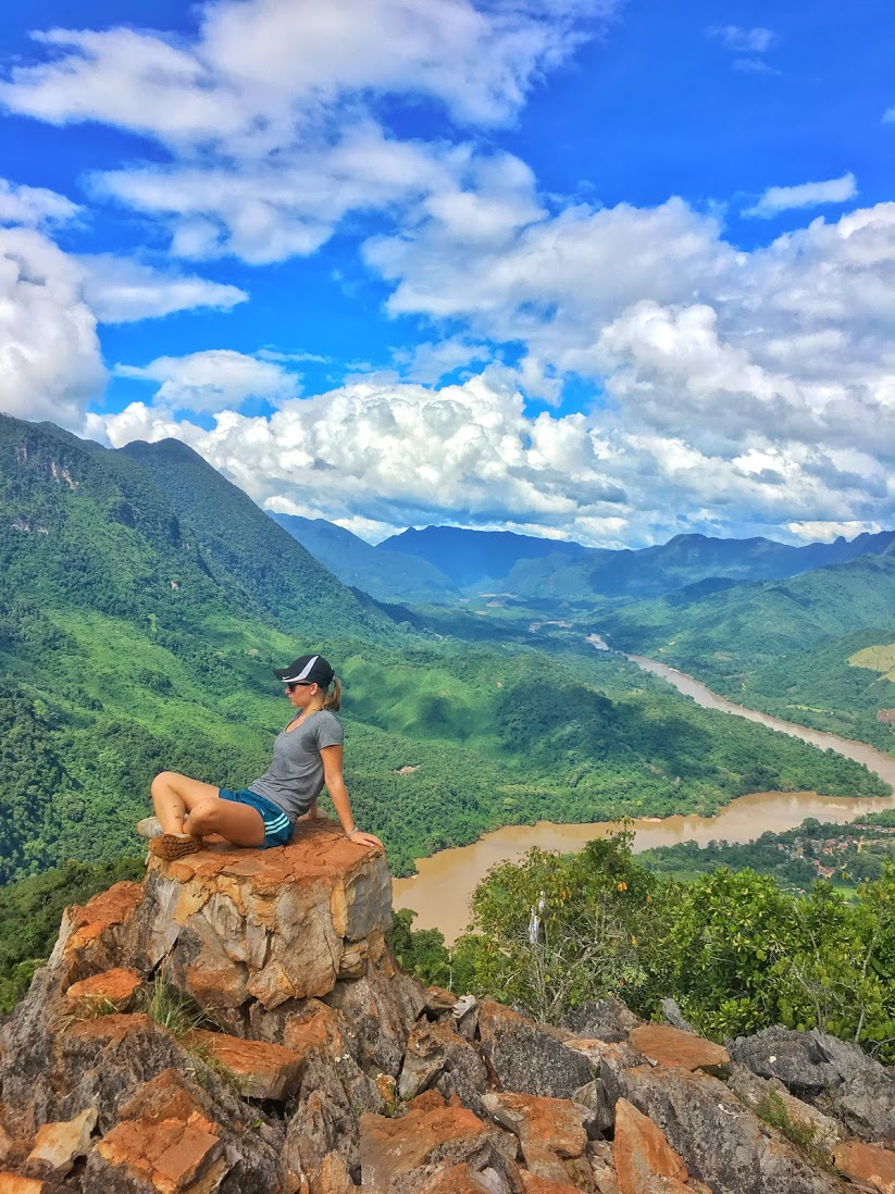 Woman sitting on a rock outcropping at the top of a viewpoint overlooking Nong Khiaw, Laos