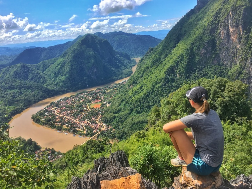 Traveler sitting at the top of a viewpoint in Nong, Khiaw Laos looking over a winding Nam Ou river and limestone mountains