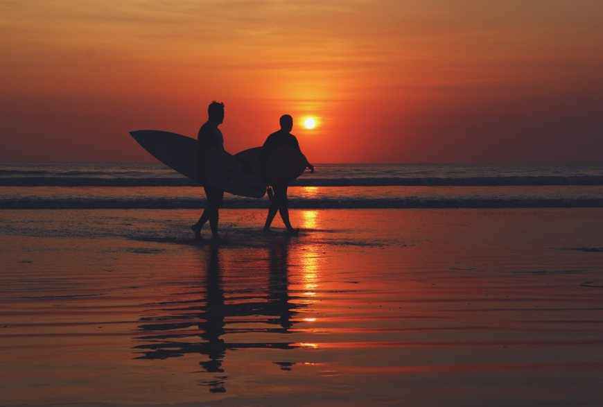Two surfers walking down the beach at sunset