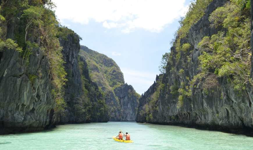 Two people kayaking in a yellow kayak down a waterway in El Nido, Palawan as rock crags jut out of the water