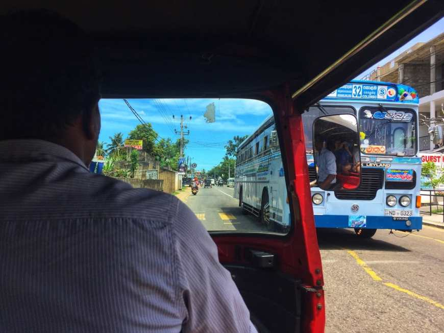 Image shot from the inside of a red tuk tuk looking forward to the driver in a button down as we drive past a large blue buss