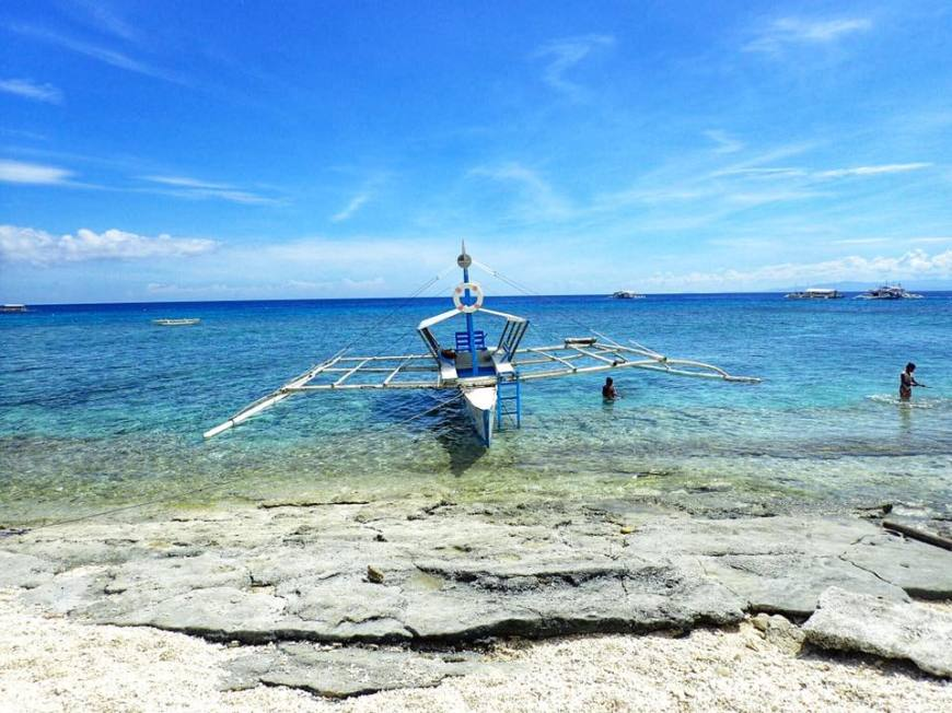 Filipino double outrigger crafts boat, called banca, floating just off the beach on a bright blue sea under the sun