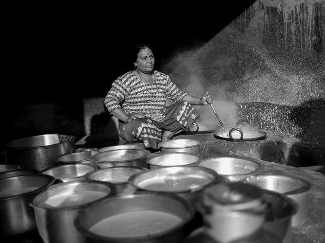 grayscale photography of woman cooking while holding a ladle in Nepal