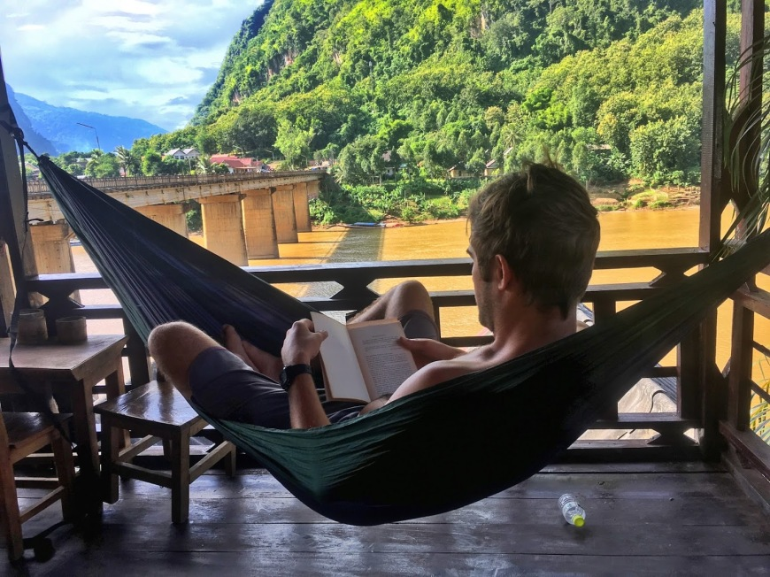 TJ sitting in his ENO hammock reading a book on our balcony above the Nam Ou river in Nong Khiaw, Laos
