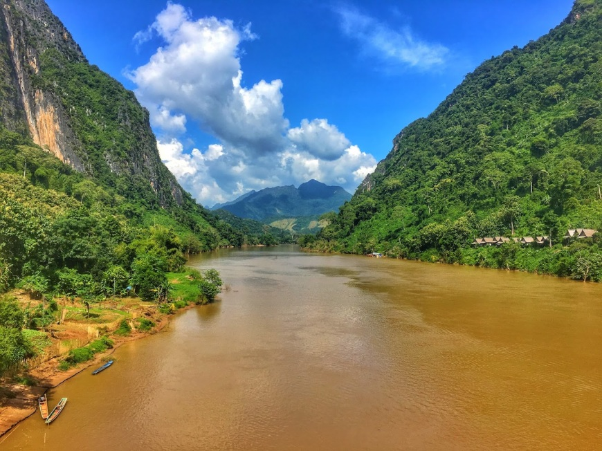 Expansive Nam Ou river that runs through the middle of Nong Khiaw, Laos with lush, green mountains on either side