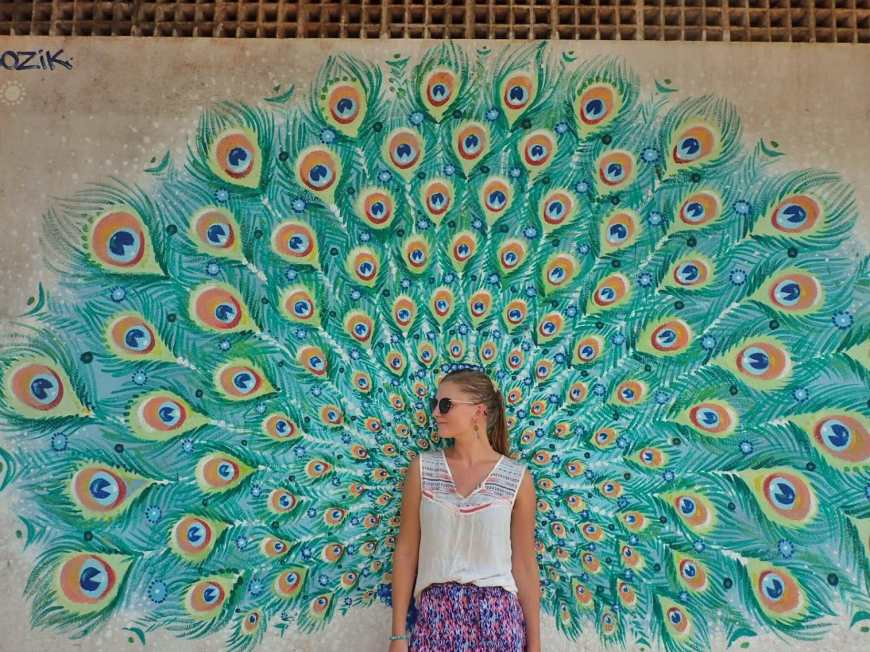 Woman standing in front of a peacock mural as the feathers span out behind her like wings