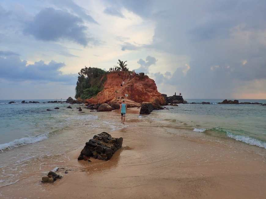 Tiny island connected by a sandbar to main Mirissa Beach in Sri Lanka