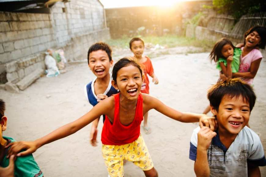 Group of filipino boys and girls laughing playing and smiling together as they look at the camera